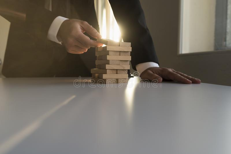 Businessman building a tower of wooden blocks royalty free stock images