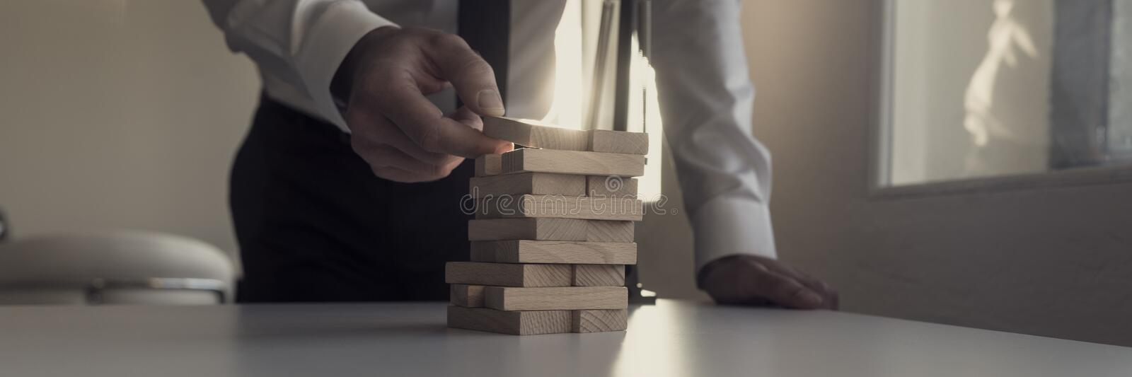 Businessman building tower of wooden bricks with a bright light stock images