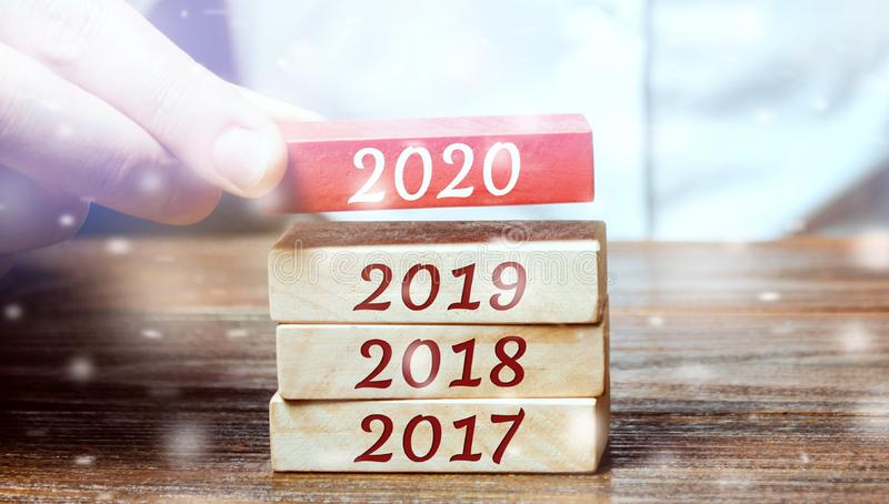 Businessman builds wooden blocks 2020. The concept of the beginning of the new year. New goals. Next decade. Trends and changes in. The world. Build plans and royalty free stock photography