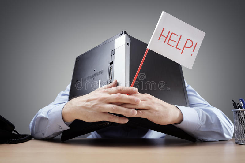 Businessman burying his head under a laptop asking for help stock photo