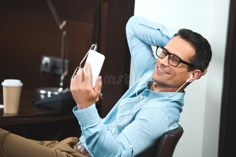 businessman in business casual clothing listening to music in headphones and reading royalty free stock photos