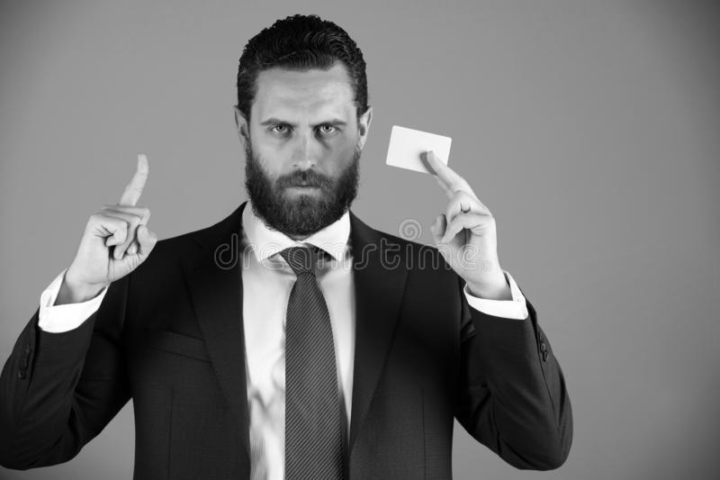 Businessman with business or credit card, business ethics. Businessman or bearded man with business or credit card in blue formal outfit on grey background royalty free stock photography