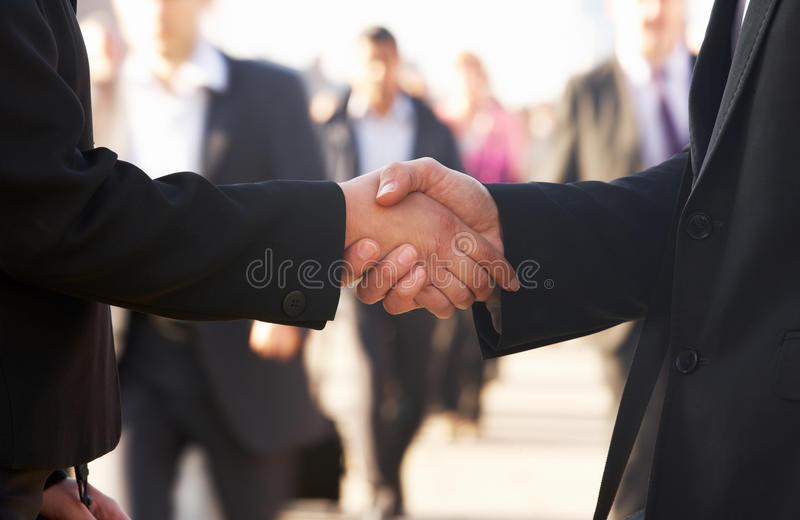 Businessman and business woman shaking hands stock images