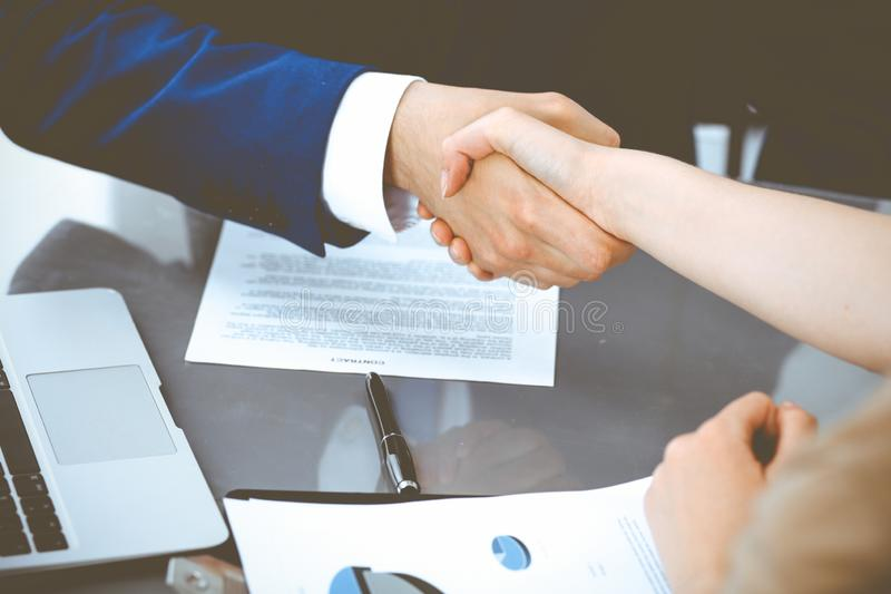 Businessman and business woman shaking hands to each other above signed contract. Success at negotiation and agreement. Businessman and business woman shaking royalty free stock photography