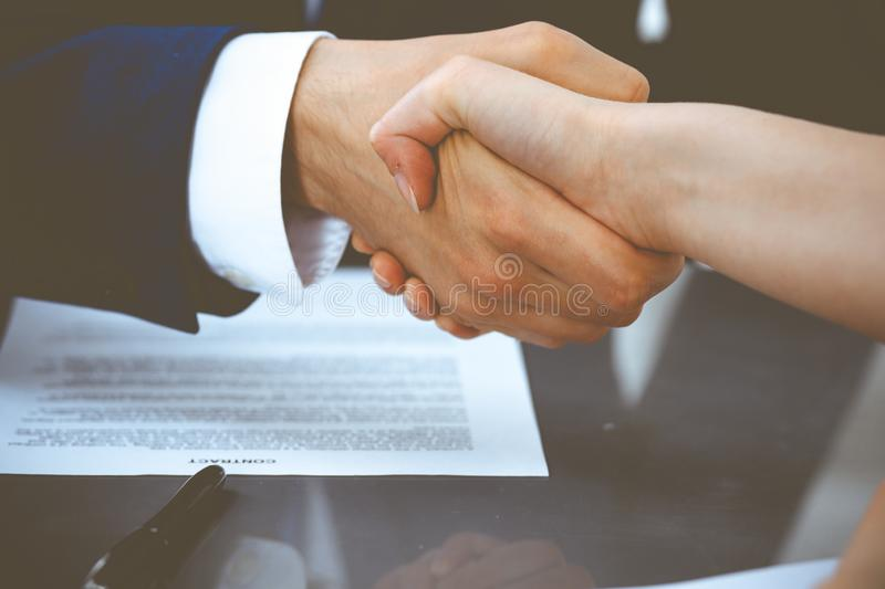 Businessman and business woman shaking hands to each other above signed contract. Success at negotiation and agreement. Businessman and business woman shaking stock photos
