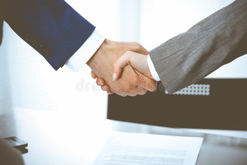 Businessman and business woman shaking hands to each other above signed contract. Success at negotiation and agreement. Businessman and business woman shaking stock photo