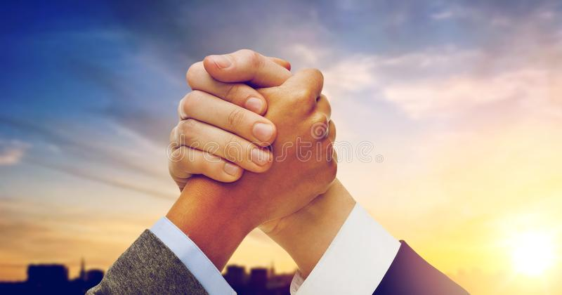 Businessman and businesswoman arm wrestling. Business, confrontation and cooperation concept - businessman and businesswoman arm wrestling over city background royalty free stock image