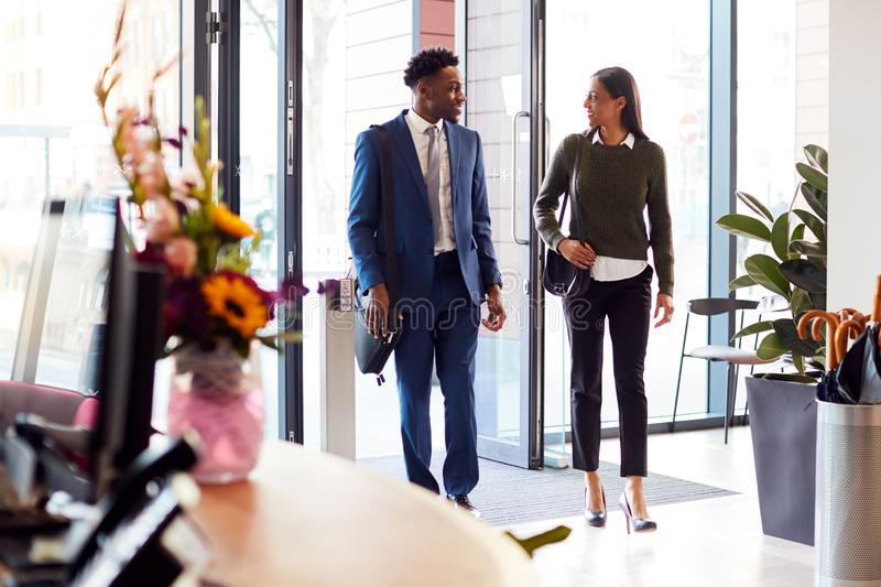 Businessman And Businesswoman Arriving For Work At Office Walking Through Door stock photos