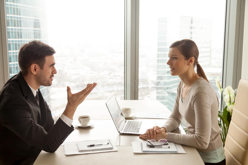 Businessman and businesswoman discussing work at office desk nea stock photography