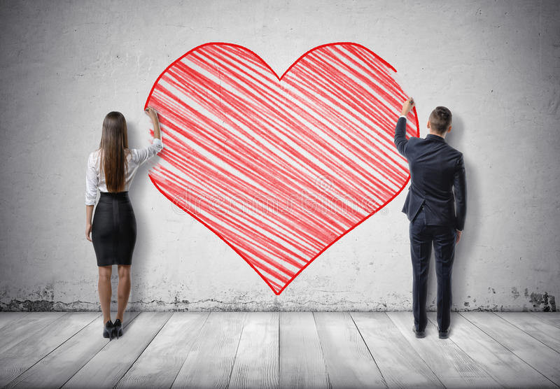 Businessman and businesswoman drawing big red heart on concrete wall. Back view of a businessman and a businesswoman drawing big red heart on concrete wall royalty free stock photography
