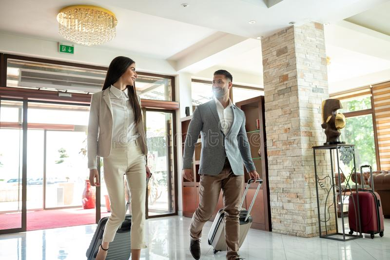 Businessman and a businesswoman entering the lobby royalty free stock image