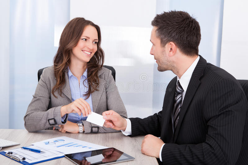 Businessman and businesswoman exchanging visiting card at office desk royalty free stock photos