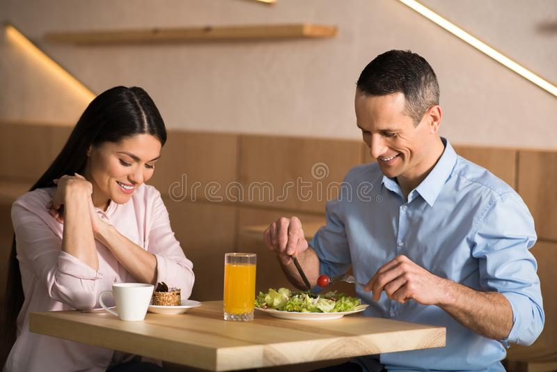 Businessman and businesswoman having lunch in cafe. Smiling businessman and businesswoman having lunch in cafe together royalty free stock photo