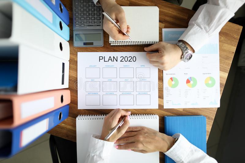 Businessman and businesswoman make work plan 2020. On office table with folder paper background. Business paperwork concept stock image