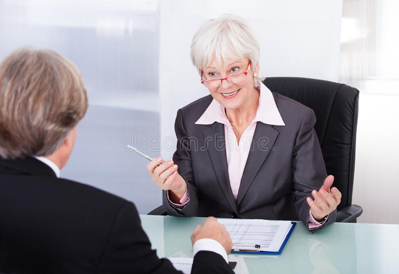 Businessman and businesswoman in meeting. Mature Businesswoman And Businessman Discussing At Workplace royalty free stock photo