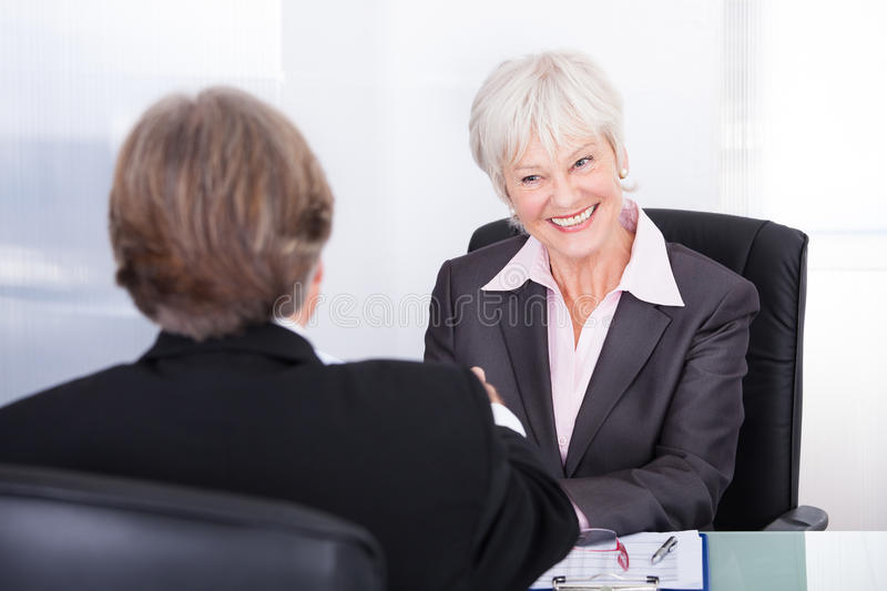 Businessman and businesswoman in meeting. Mature Businesswoman And Businessman Discussing At Workplace stock image