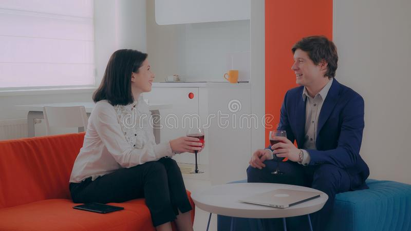 Businessman and businesswoman relish wine in flat. Young couple sitting in apartment with modern interior talking and drinking red wine. Business partners stock image