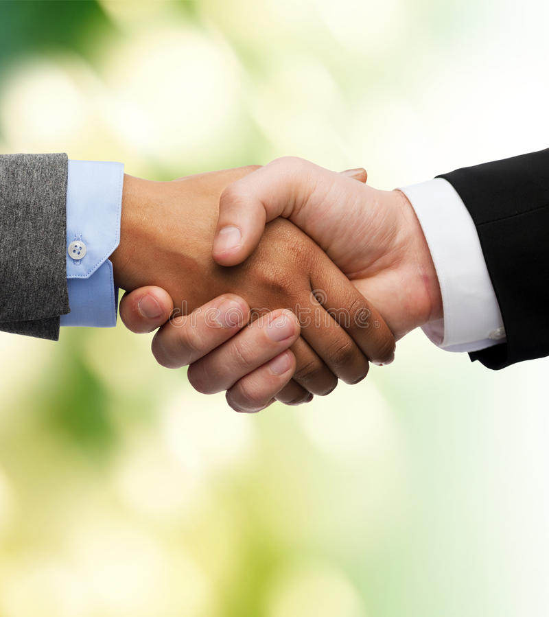 Businessman and businesswoman shaking hands stock images
