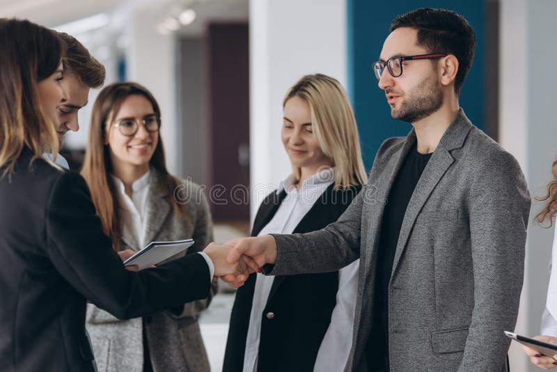 Businessman and businesswoman shaking hands in conference room. Talking by contract stock photos