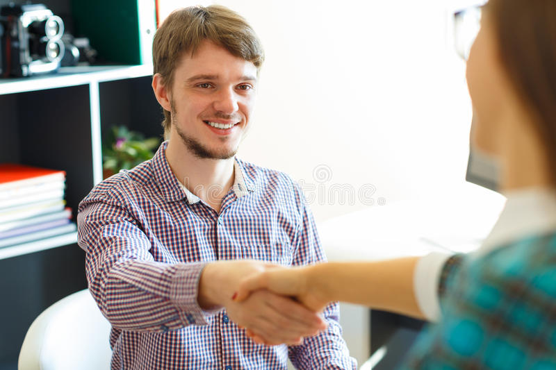 Businessman and businesswoman shaking hands in office. Young businessman and businesswoman shaking hands in office stock photos