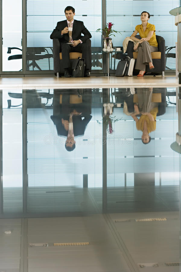 Businessman and businesswoman sitting in lobby, man holding cup, reflection on shiny floor stock photos