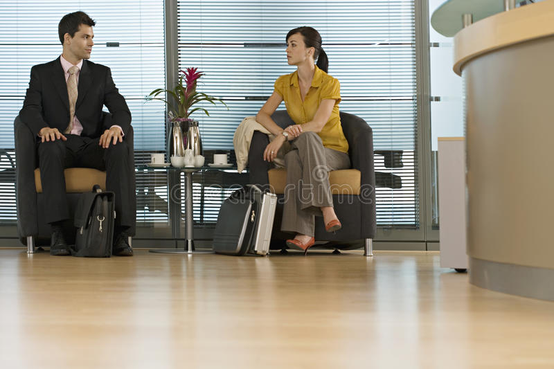Businessman and businesswoman sitting in office reception area, face to face, surface level stock photo