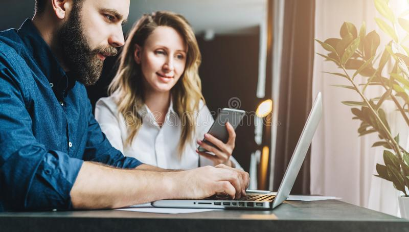 Businessman and businesswoman sitting at table in front of laptop and looking at monitor. Teamwork, online marketing. royalty free stock photography