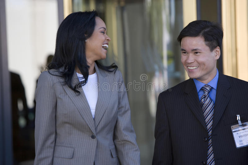 Businessman and businesswoman standing outside building, woman laughing stock images