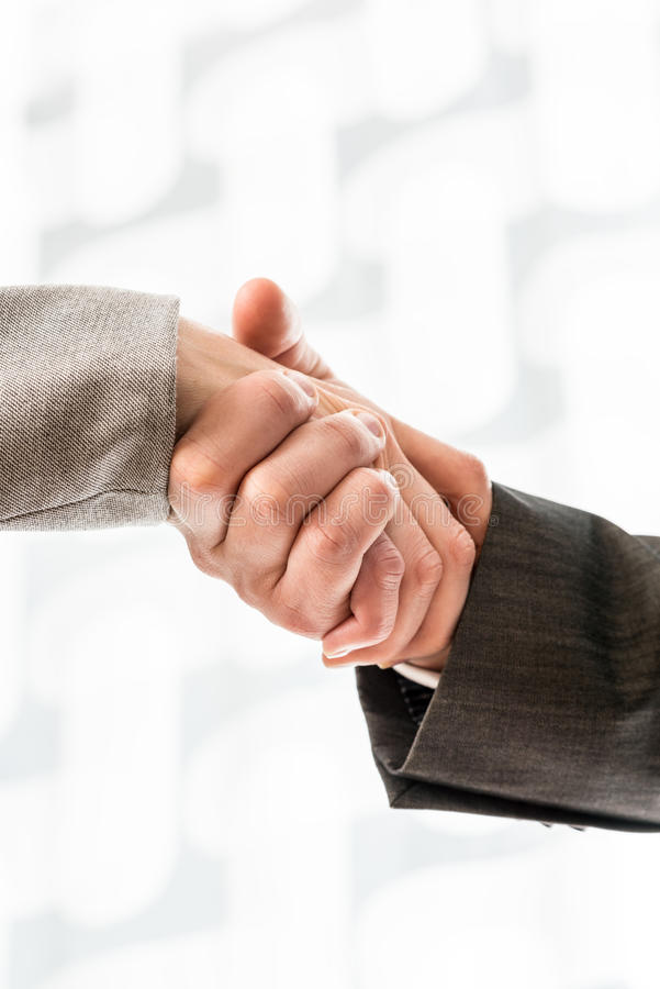Businessman and businesswoman in suits shaking hands. Over a blurred abstract background conceptual of a deal, agreement, partners or greeting, vertical format stock photography