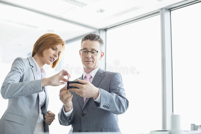 Businessman and businesswoman using cell people in office royalty free stock photos