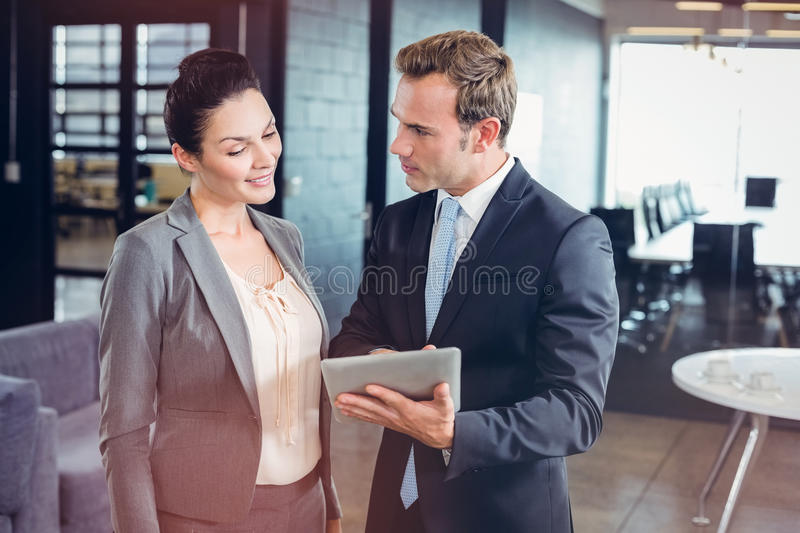 Businessman and businesswoman using digital tablet. In office stock photos