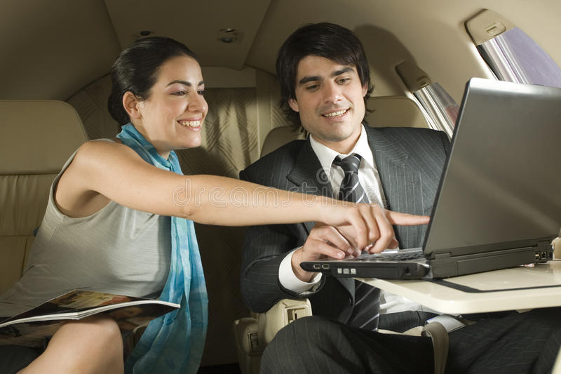Businessman and a businesswoman using a laptop in a private airplane