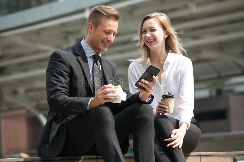 Businessman and businesswoman using smartphone  eating breakfast and drinking coffee together in city outdoors.Colleagues excited stock photos