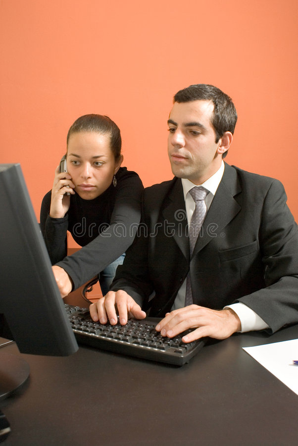 Businessman and Businesswoman - Vertical. Businessman and woman hover over a computer royalty free stock photo