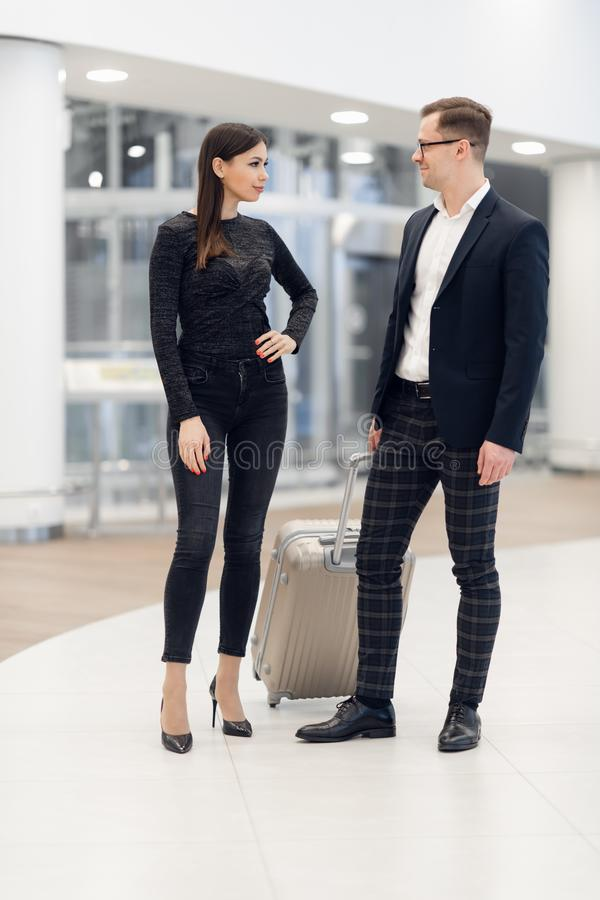 Businessman and Businesswoman Walking with Rolling Suitcase royalty free stock photography