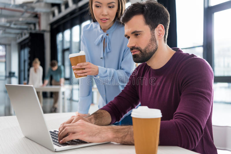 Businessman and businesswoman working with laptop in small business office royalty free stock images