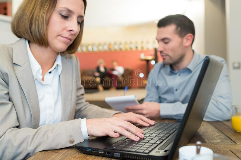 Businessman and businesswoman working during lunch royalty free stock images