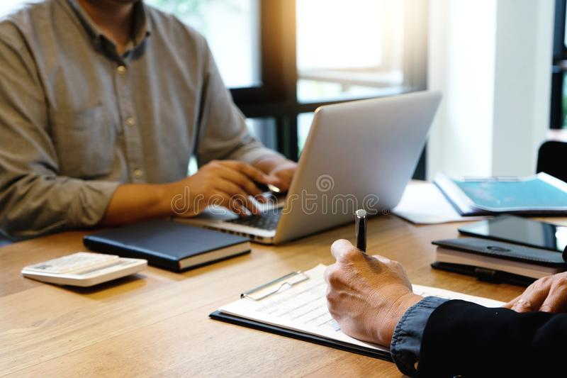Businessman and businesswoman working to analyses market stock. Chart on wood table in coffee shop stock images