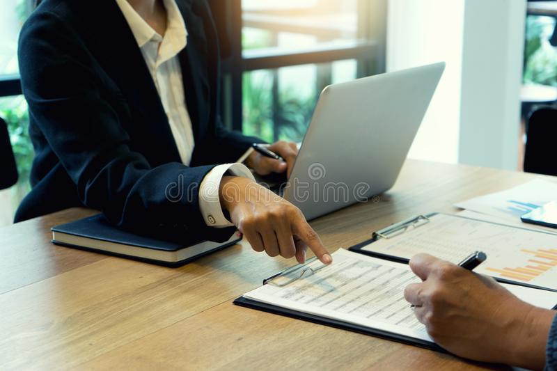 Businessman and businesswoman working to analyses market stock. Chart on wood table in coffee shop royalty free stock photos