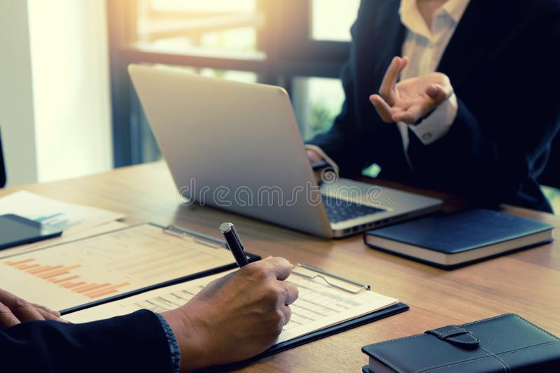 Businessman and businesswoman working to analyses market stock. Chart on wood table in coffee shop stock photography