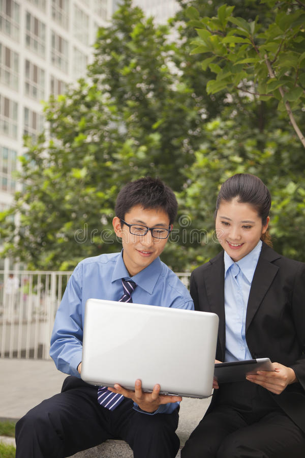 Download Businessman And Businesswoman Working Together Outdoors On The Laptop Stock Photo - Image: 31127930