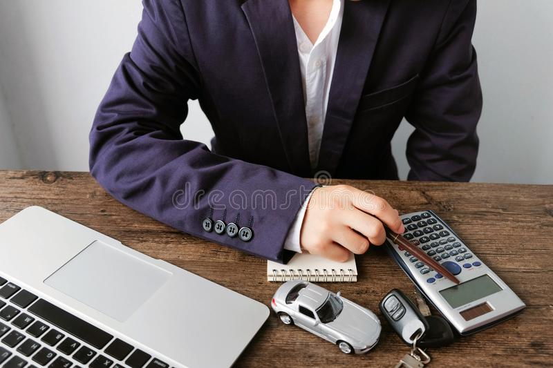 Businessman is calculating car purchase cost with calculator ,laptop ,car model ,key and blank notebook on wooden table.. royalty free stock images