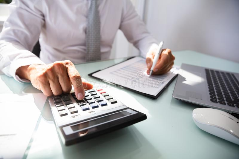Businessman Calculating Invoice. Close-up Of A Businessman`s Hand Calculating Invoice With Calculator royalty free stock photo
