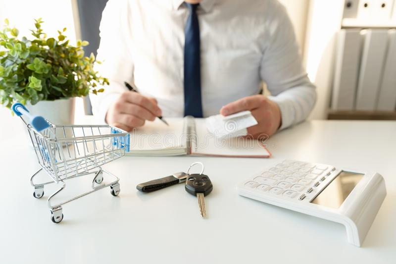 Businessman calculating shopping expenses for car purchase, holding receipts in hand. Empty shopping cart and car keys in front stock image