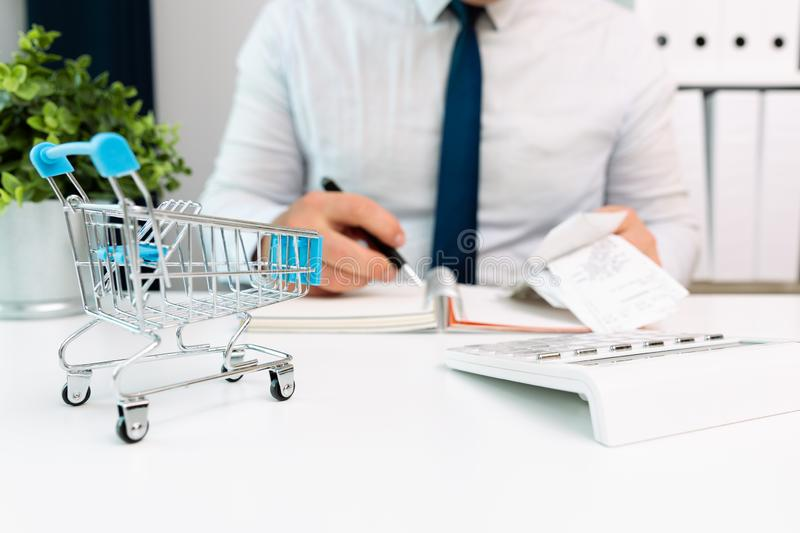 Businessman calculating shopping expenses, holding receipts in hand. Empty shopping cart in front. Home finances, investment, stock photo