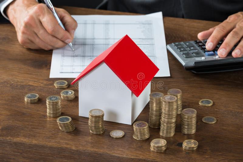 Businessman Calculating Tax By Model House And Coins stock photos