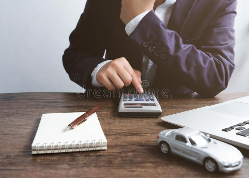 Businessman is calculating for trading a car with car models not. Ebooks and laptop on the desk, concept of selling contracts royalty free stock photography