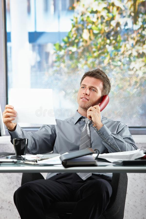 Download Businessman  On Call Looking At Paper Stock Photo - Image: 12801266