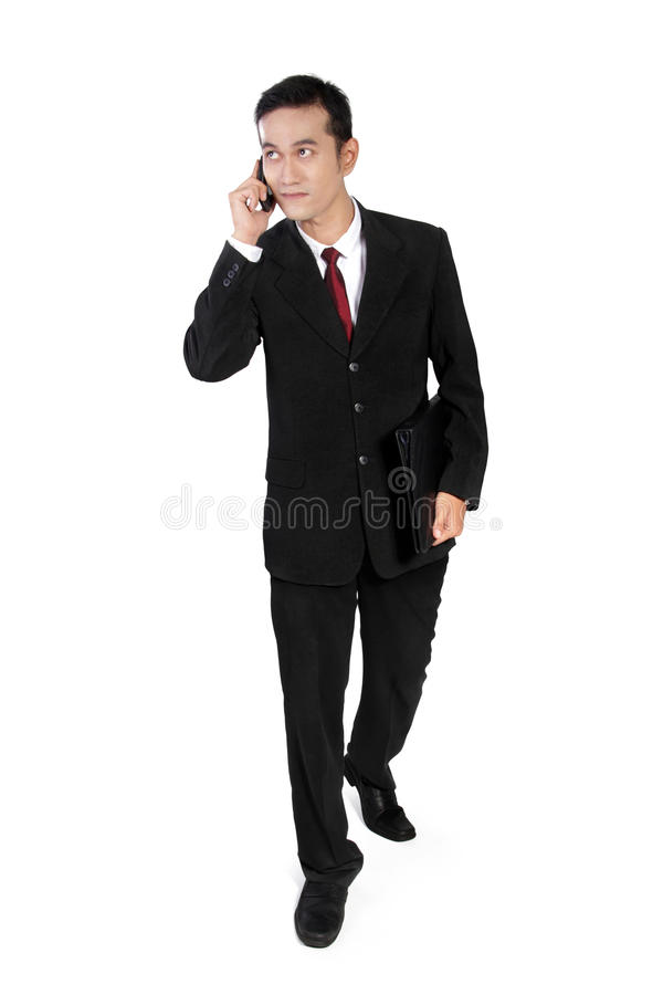 Businessman on call, looking up and walking royalty free stock photos