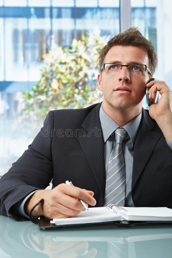 Businessman on call taking notes royalty free stock photos